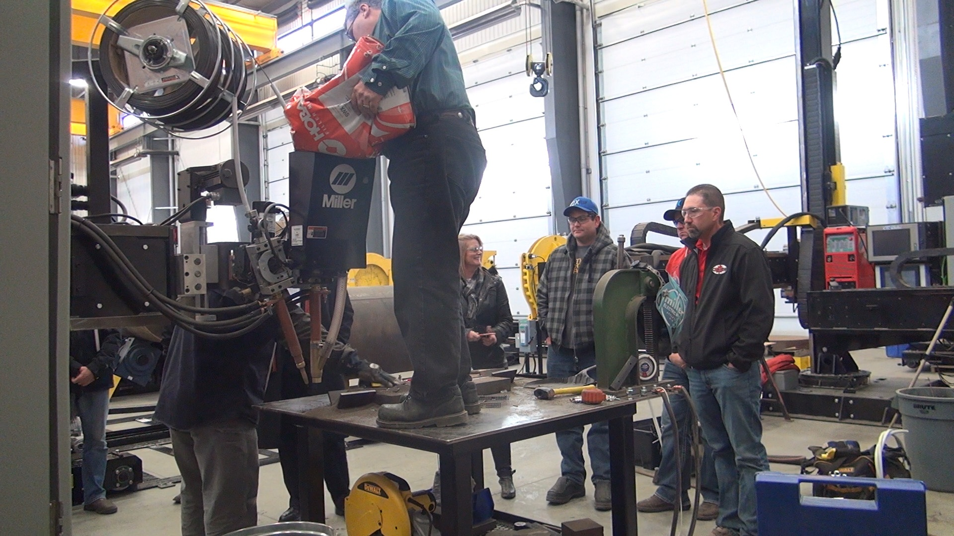 flux being refilled into hopper of the welding manipulator